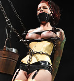 Beautiful redhead in latex and chains