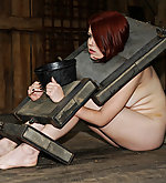Naked redhead put in stocks and caned