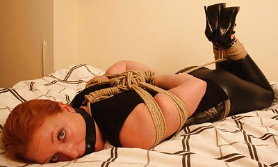 Redhead roped and hogtied on her bed