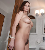 Kyla tied naked to a wooden pole in a bathroom
