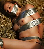 Taped up babe rolling down a haystack