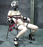 Fixed with leather straps, gagged, dildoed