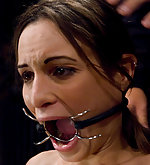 Amber is bound to the floor and ring-gagged